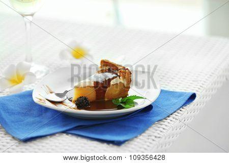 Delicious cake under chocolate glaze with blackberry on blue serviette