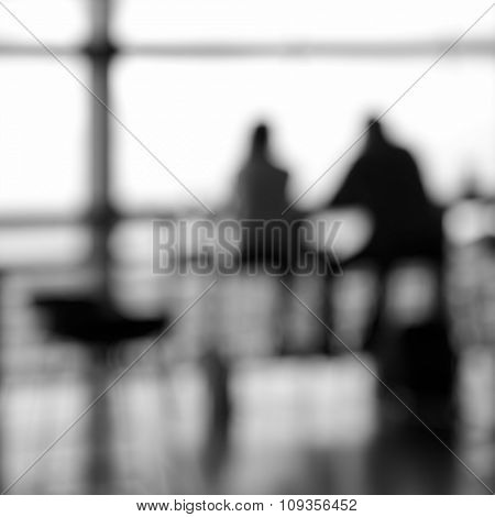 Couple at airport cafe. Black and white and out of focus image.
