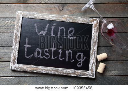 Square frame with wine glass on wooden background
