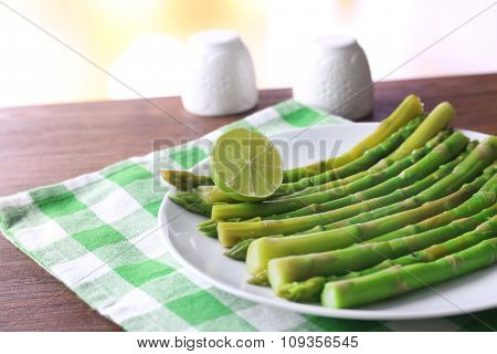 Fresh asparagus with lime on white plate with checkered cotton serviette