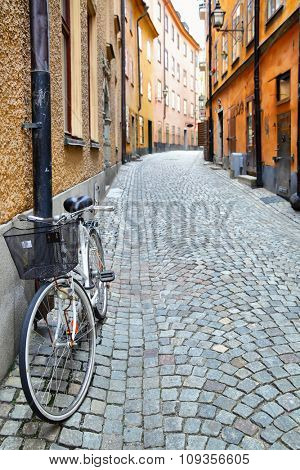 Old street in Stockholm, Sweden. Shallow DOF, focus on the bike