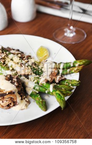 Delicious dish with asparagus and mushrooms on served wooden table in the restaurant, close up