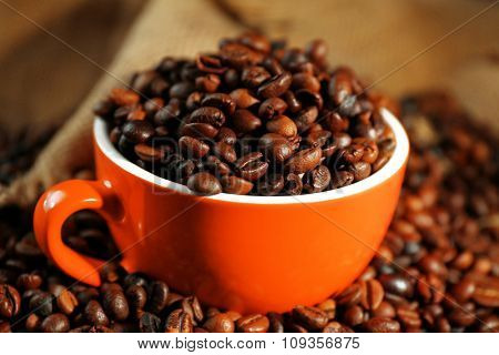 A red cup and aromatic coffee beans scattered on sacking background
