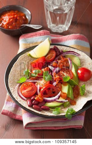 vegan taco with avocado tomato kidney beans and salsa