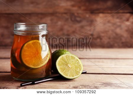 Iced tea with lemon on wooden background