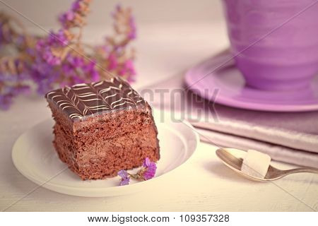 Served table with chocolate cake and a cup of tea on white wooden background