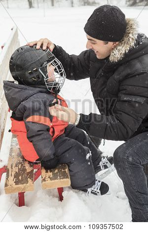 father help his child to put his helmet