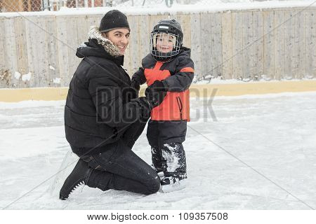 family playing at the skating rink in winter.