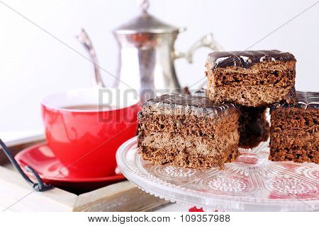 Served table with chocolate cakes, a cup of tea and teapot close-up