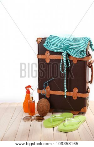 Valise with summer items on wooden board on white background