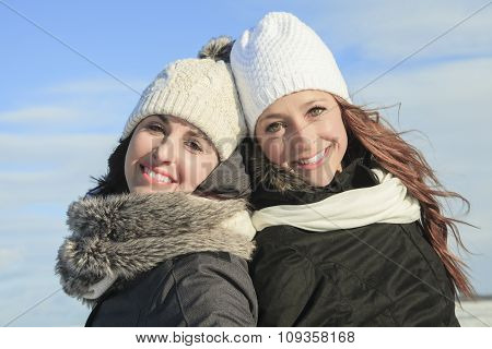 Two young girls having fun in winter park