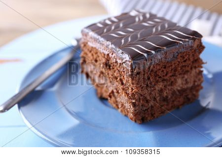Sweet chocolate cake on blue plate on wooden table, close up