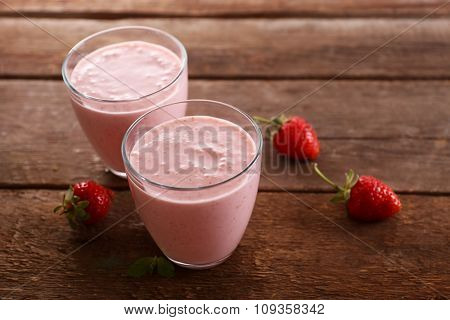 Fresh strawberry yogurt with berries around on wooden background