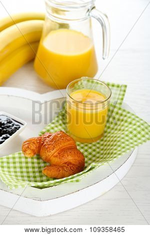 Heart shaped plate with croissant, jam and orange juice on white table