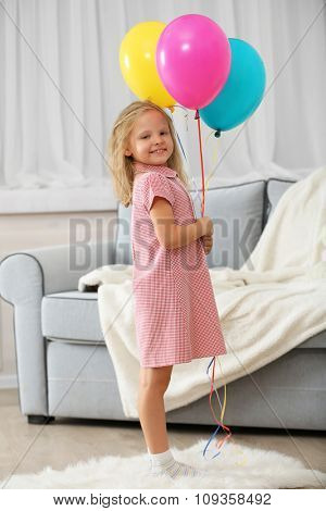 Little girl with balloons in the room