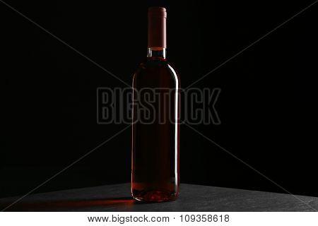 A bottle of wine, on grey-black background