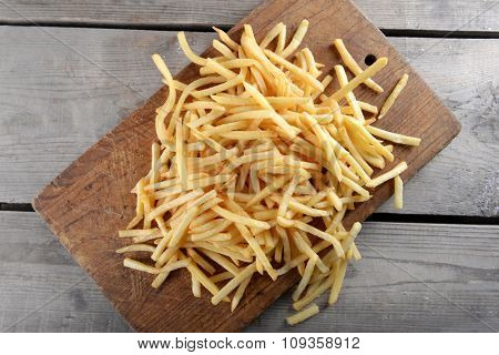 French fried potatoes on cutting board