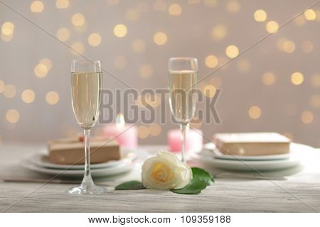 Glasses of wine and a white rose, on blurred background