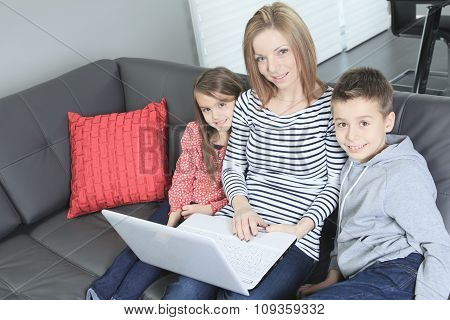 Friendly family sitting on the sofa with Labtop