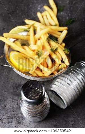 French fries with lemon and salt in sieve on table
