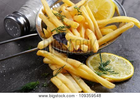 French fries with lemon and salt in sieve on table, close-up