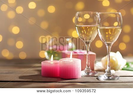 Glasses of wine, white roses and candles, on blurred background