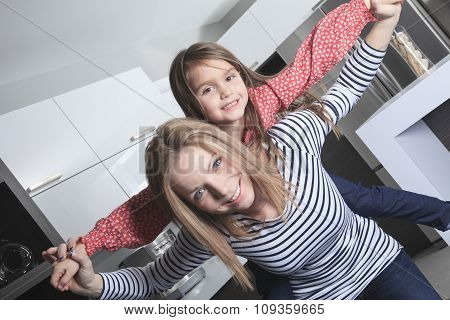 Mother with daughter standing in kitchen. Interior portrait.