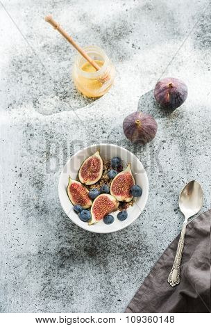Healthy breakfast. Bowl of oat granola with yogurt, fresh blueberries and figs over grunge grey back