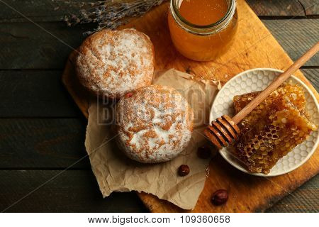 Honeycombs on plate, hot buns on wooden background