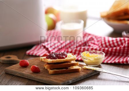 Served table for breakfast with toast, milk and jam, close-up