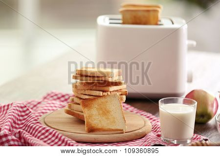 Served table for breakfast with toast, milk and honey, on blurred background