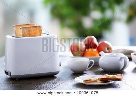 Served table for breakfast with toast, coffee and fruit, on blurred background
