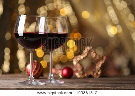 Red wine and Christmas ornaments on wooden table on golden background