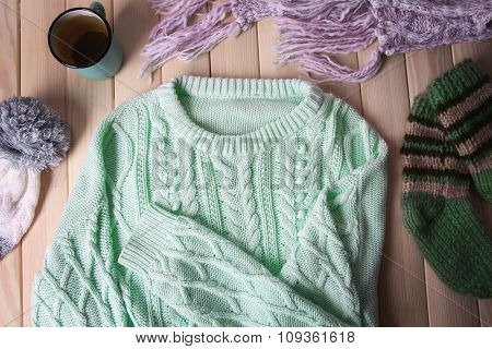 Mug of tea and warm clothes on wooden background