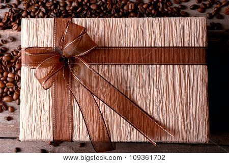 Beautiful gift with bow and coffee grains on wooden background