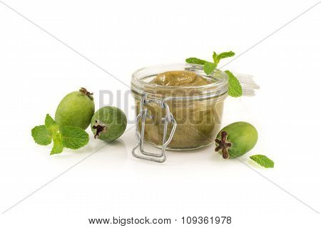 Feijoa homemade jam with fresh mint in a glass jar, isolated on white background.