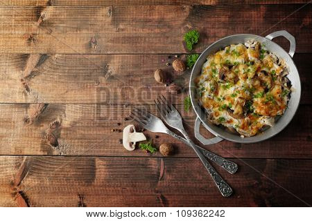 Roasted mushrooms, chicken and cheese gratin in pan, on wooden background