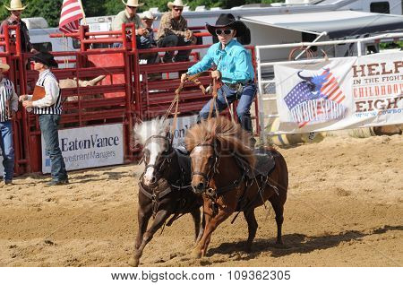 A Standing Teenage Girl Riding Two Running Ponies