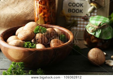 Mushrooms in wooden bowl and marinated mushrooms in jar on wooden surface