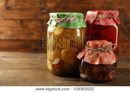 Jars with pickled vegetables on wooden background
