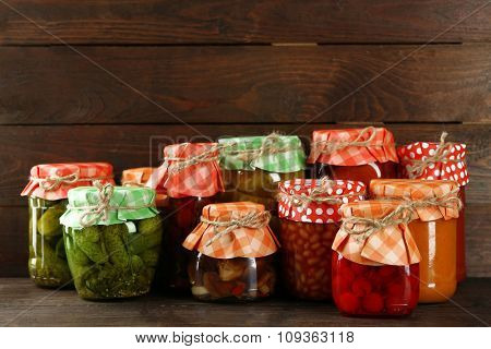 Jars with pickled vegetables and beans on wooden background