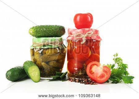 Jars of canned tomatoes and cucumbers isolated on white