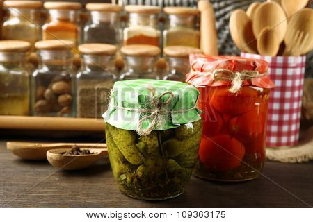 Jars with pickled vegetables and beans, spices and kitchenware on wooden background