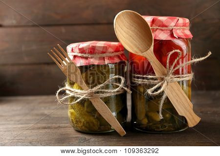 Jars with pickled vegetables on wooden background