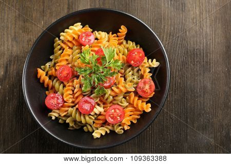 Delicious macaroni dish in black bowl on wooden background