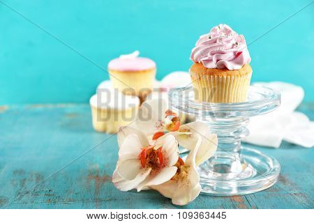 Tasty cupcakes on stand, on color wooden background