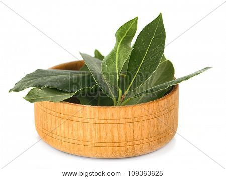 Fresh bay leaves in wooden bowl, isolated on white