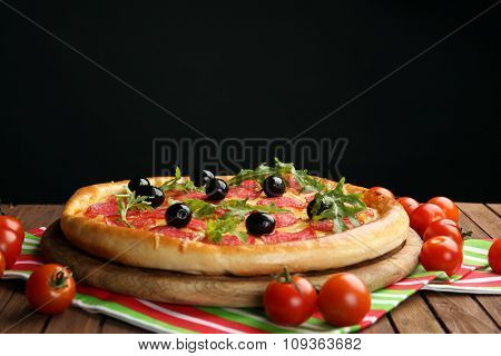 Tasty pizza with salami and olives decorated with tomatoes on wooden table against black background