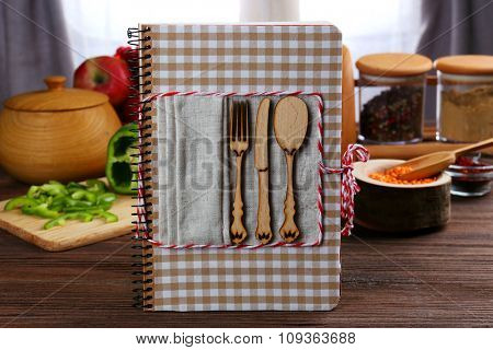 Recipe book and ingredients for cooking on a table in kitchen