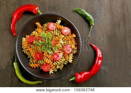 Delicious macaroni dish in black bowl on decorated with pepper wooden table